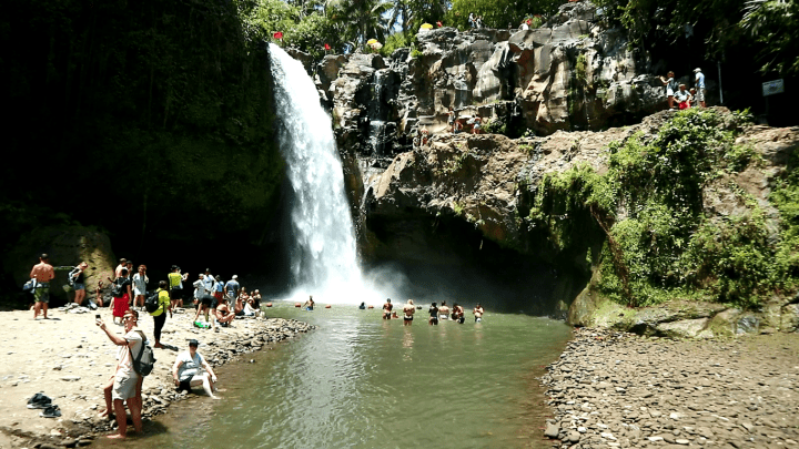 an-overall-view-over-tegenungan-waterfall-in-bali-near-ubud-with-water-falling-down-and-people-siwmming-and-taking-pictures